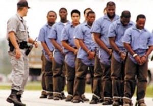 black men shackled and led by a white prison guard